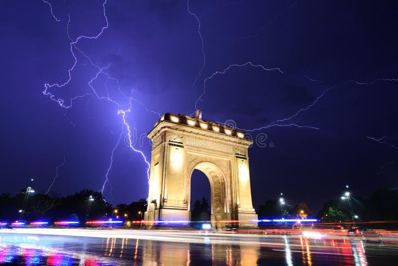Bucharest Triumph łuk w lekkiej burzy nocą obrazy stock