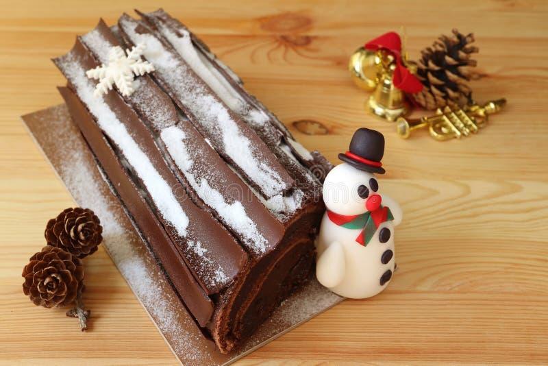 Buche de Noel或巧克力圣诞柴蛋糕用逗人喜爱的雪人小杏仁饼和干燥杉木锥体,在木表上的圣诞节装饰品 库存照片