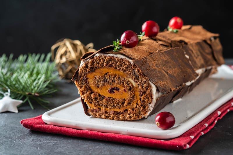 Buche de Noel Dessert traditionnel de Noël, gâteau de rondin de Noël de Noël avec de la crème de chocolat, canneberge Sur le gris photos stock