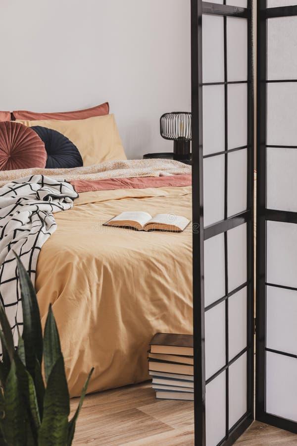 Buchen Sie über gelbe Bettdecke im kleinen gemütlichen Schlafzimmer mit Ingwer-Akzenten stockfoto