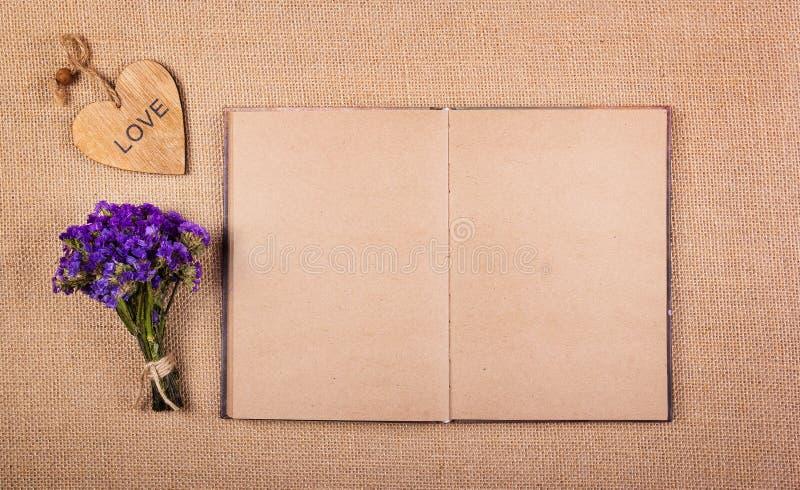 Buchen Sie mit Leerseiten, einem Blumenstrauß von wilden Blumen und Grußherzen Herz gemacht vom Holz und von den Blumen Romantisc lizenzfreie stockbilder