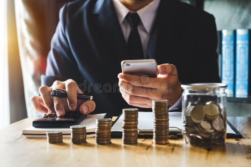 Buchhalter, der an Schreibtisch im Büro unter Verwendung des Taschenrechners und des Smartphone arbeitet, um Budget zu berechnen lizenzfreie stockfotos
