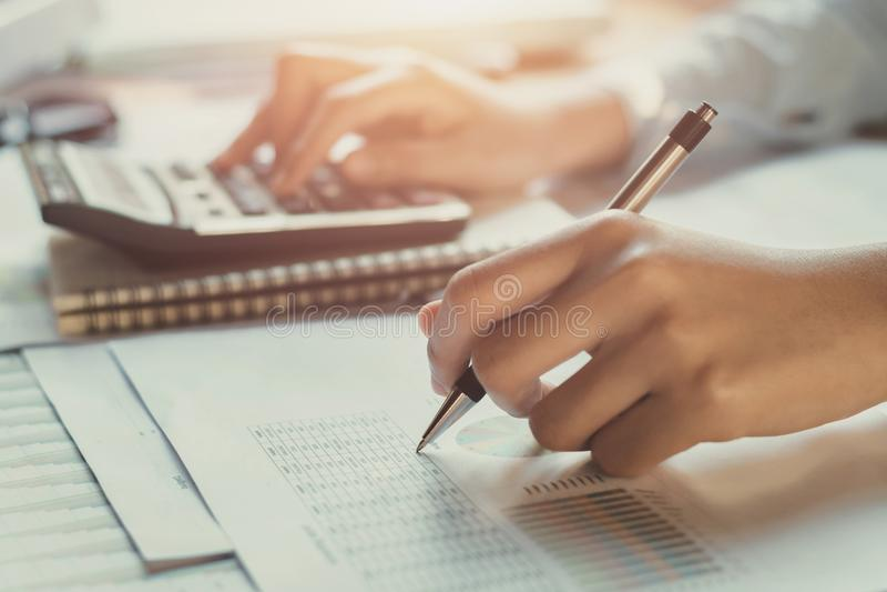 Buchhalter, der an Schreibtisch zur Anwendung des Taschenrechners arbeitet lizenzfreie stockfotografie