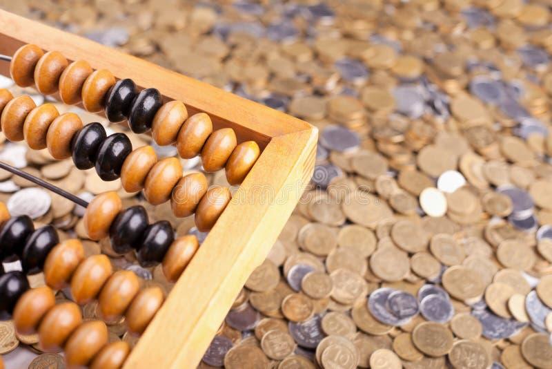 Buchhaltungrechenmaschine und -münzen stockfoto