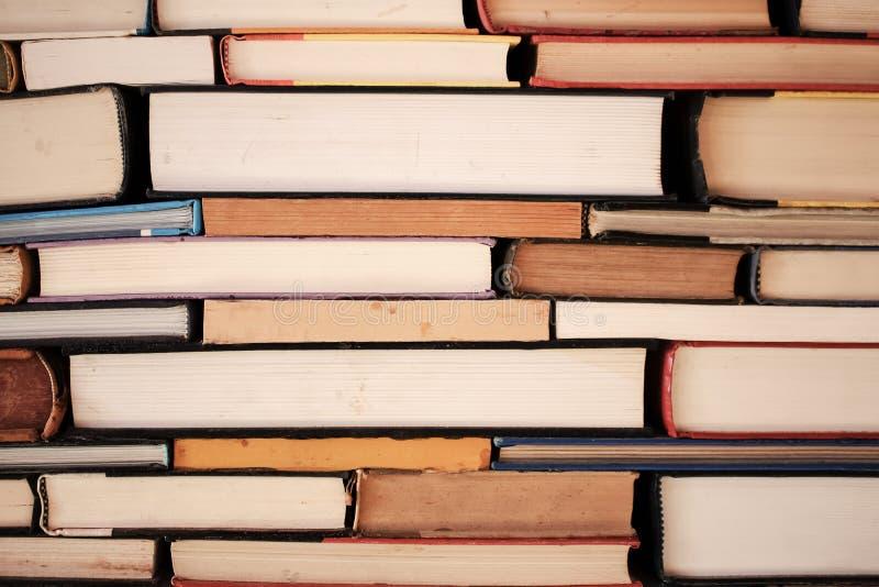 Buchhintergrund - Ansicht des Randes der alten Bücher des gebundenen Buches gestapelt fast wie Ziegelsteine - Nahaufnahme lizenzfreie stockbilder