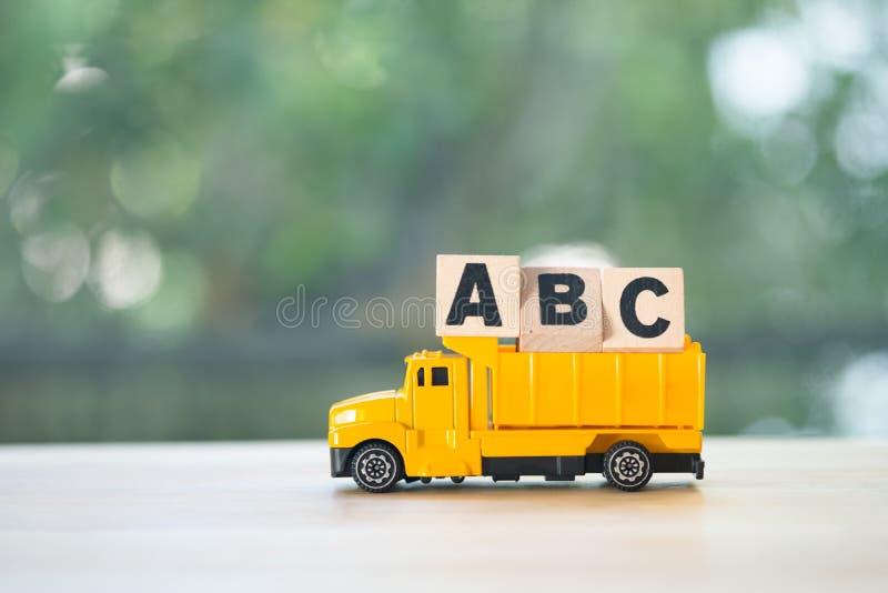 Buchstabe a, b, hölzerne Würfelblöcke c-Alphabetes gesetzt auf Spielzeugkleintransporter stockfoto