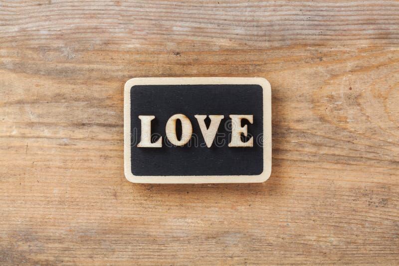 Buchstabe-Liebe auf hölzernem Hintergrund stockbild