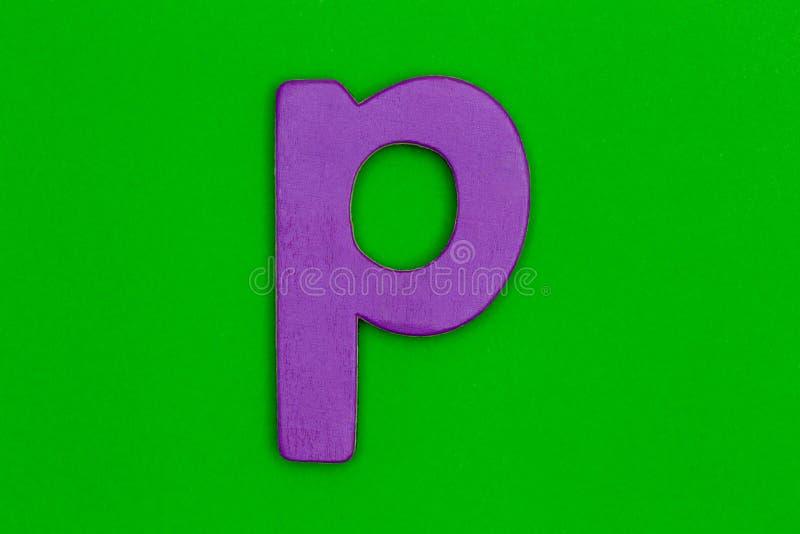 Buchstabe p machte vom hölzernen gemalten Purpur auf grünem Hintergrund stockfotos