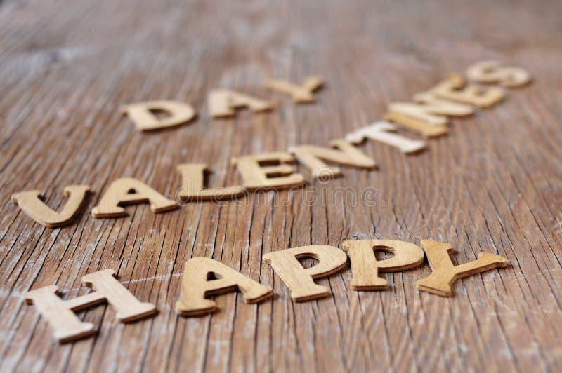 Buchstaben, die den glücklichen Valentinsgrußtag des Satzes auf einer hölzernen SU bilden stockfotografie