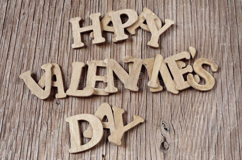 Buchstaben, die den glücklichen Valentinsgrußtag des Satzes auf einer hölzernen SU bilden lizenzfreies stockbild