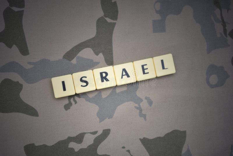Buchstaben mit Text Israel auf dem kakifarbigen Hintergrund Grüne taktische Schutzkleidung mit US-Streifenmarkierungsfahne und Na lizenzfreie stockfotografie