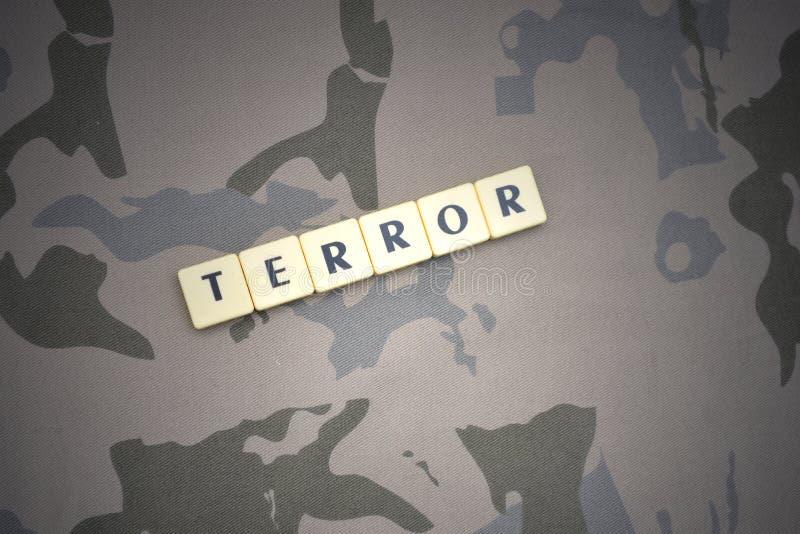 Buchstaben mit Textterror auf dem kakifarbigen Hintergrund Grüne taktische Schutzkleidung mit US-Streifenmarkierungsfahne und Nah lizenzfreies stockbild