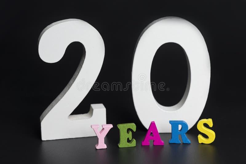 Buchstaben und Zahlen für zwanzig Jahre auf einem schwarzen Hintergrund stockbilder