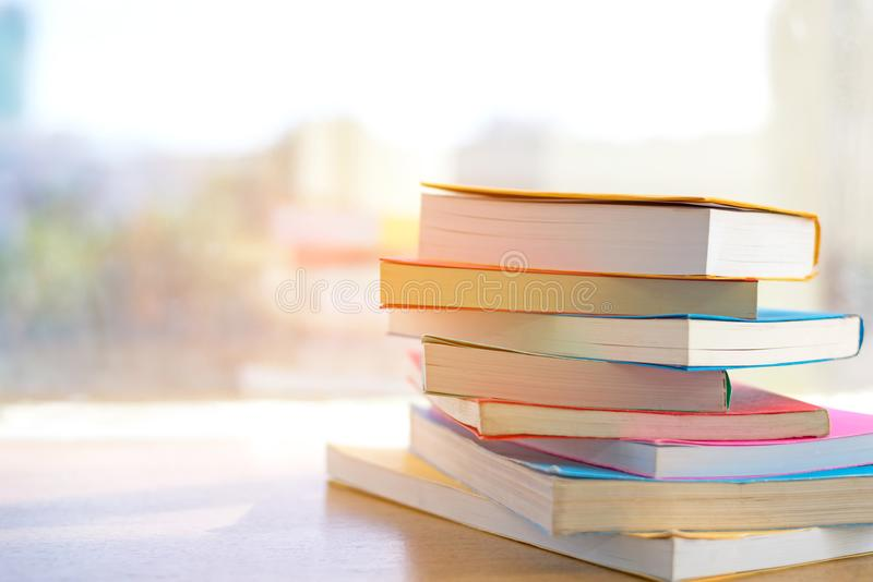 Buchstapel im Bibliotheksraum für zurück zu Schule und in der Bildung am sonnigen Tag nahe Fenster in der Bibliothek stockbild