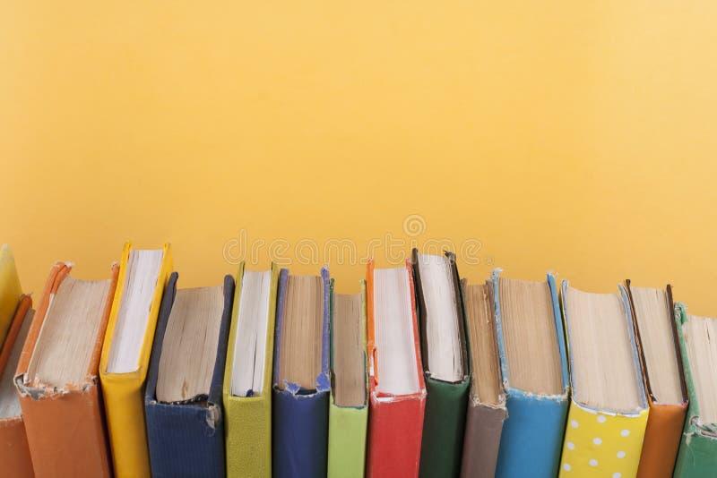 Buchstapeln Offenes gebundenes Buch reserviert auf Holztisch- und Gelbhintergrund Zurück zu Schule Kopieren Sie Raum für Anzeigen lizenzfreies stockbild