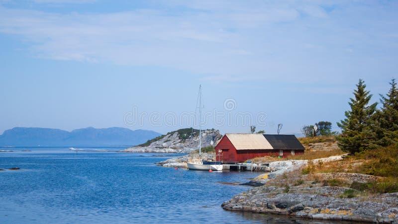 Bucht-Meerwasser-Fischer-Haus Landschafts-Norwegens Floro mit Boot lizenzfreie stockfotos