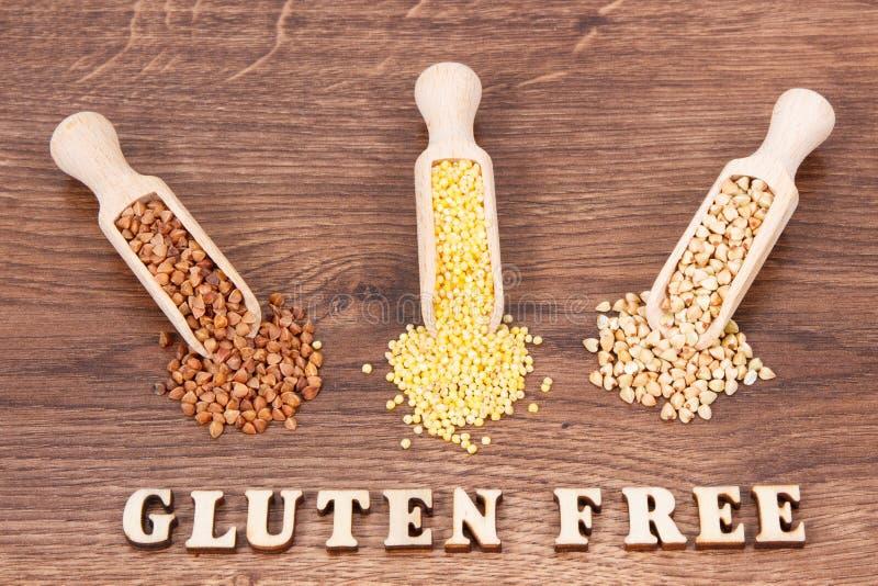 Buchweizen- und Hirsegrützen mit Schaufel auf rustikalem Brett, gesund und Gluten geben Lebensmittel frei lizenzfreie stockfotos