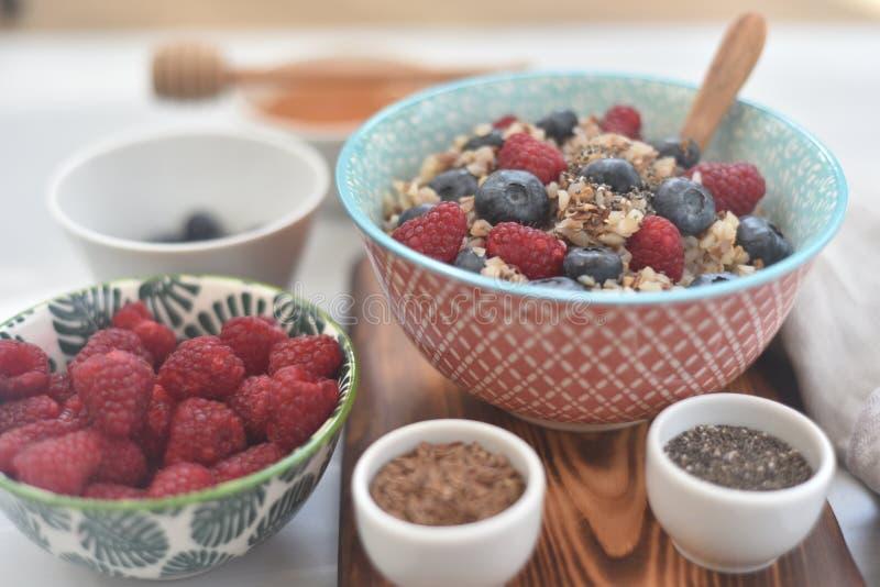 Buchweizengetreide mit den Himbeeren und Blaubeeren zum Frühstück, gesät mit chia Samen und Leinsamen, mit Honig lizenzfreies stockbild