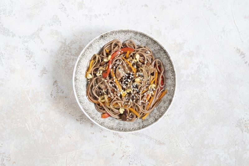 Buchweizennudeln mit dem Gemüse und Fleisch verziert mit indischem Sesam in der Schüssel auf grauem Hintergrund Beschneidungspfad lizenzfreie stockfotos