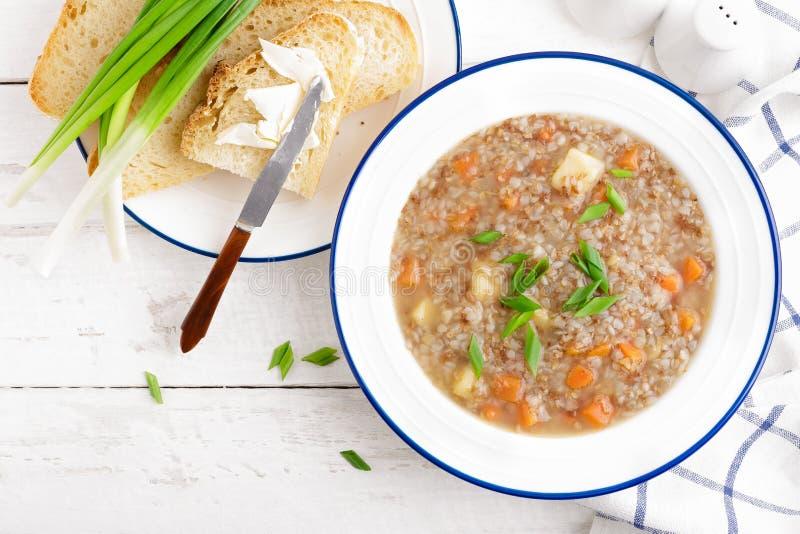 Buchweizensuppe mit Karotte und Kartoffel auf weißer hölzerner rustikaler Tabelle Gesunde vegetarische Nahrung lizenzfreie stockfotografie