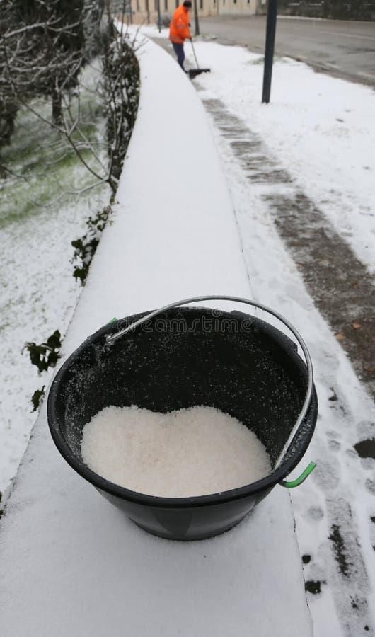 Bucket с солью для избежания падений на лед тротуара a стоковая фотография rf