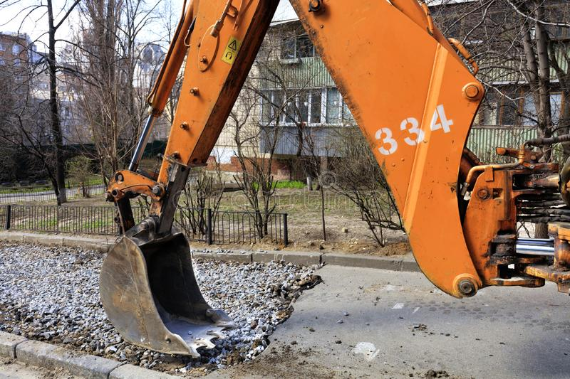 Bucket and arrow of a heavy road excavator on the repair of the sidewalk. royalty free stock image