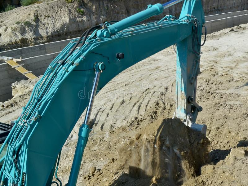 Bucket of a blue excavator has just scooped up the ground at the site of road works stock photography