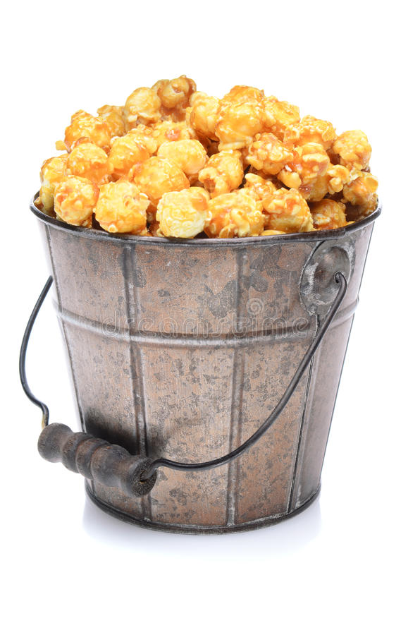 Bucket of Caramel Corn. A old fashioned bucket of caramel corn over a white background with slight reflection royalty free stock photo