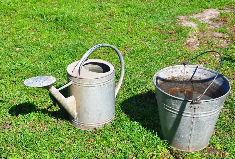 Bucket com a lata da água e molhar no fundo da grama verde fotografia de stock royalty free