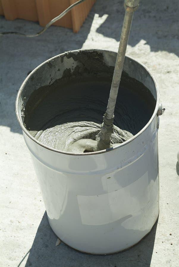 Bucket con la mezcla del pegamento en emplazamiento de la obra fotos de archivo libres de regalías