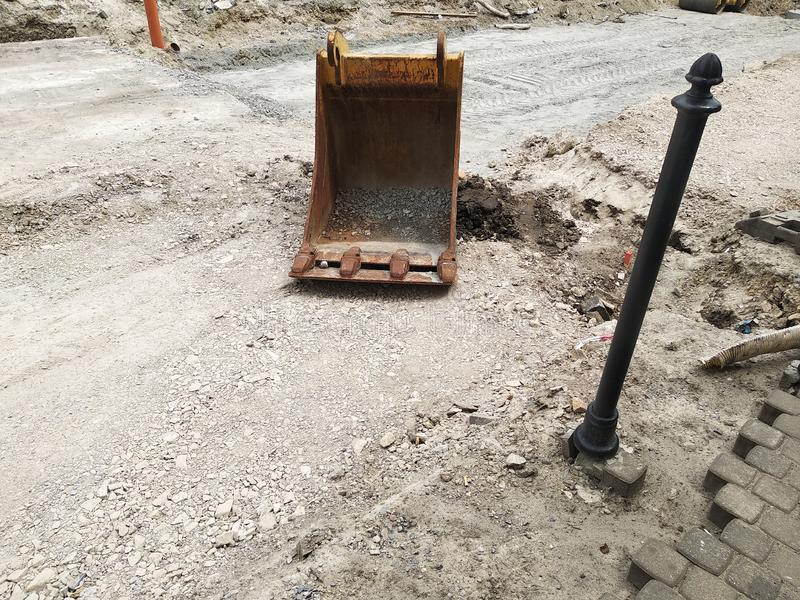 Bucket from the excavator is on the road without asphalt. repair of roads, replacement of asphalt, rail, paving slabs and fences. stock photo