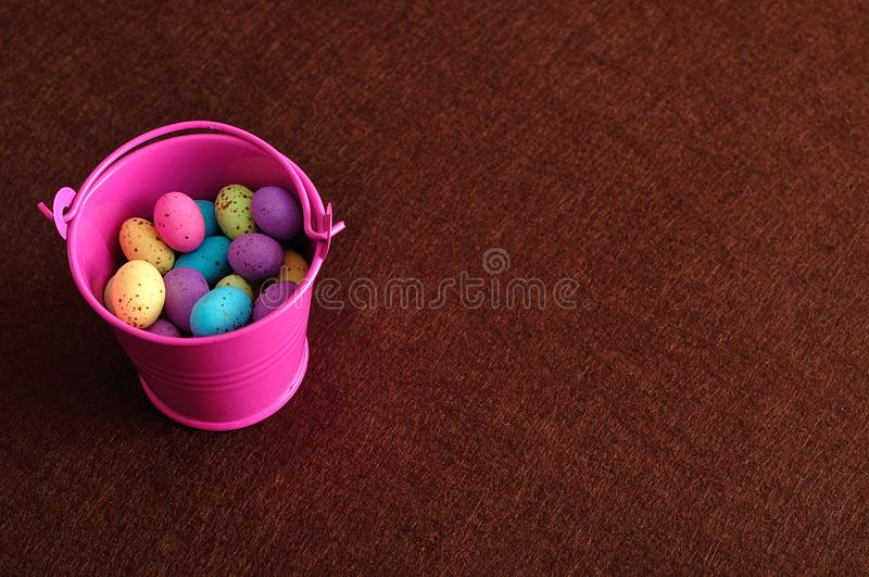 A bucket filled with speckled easter eggs. On a brown background stock images