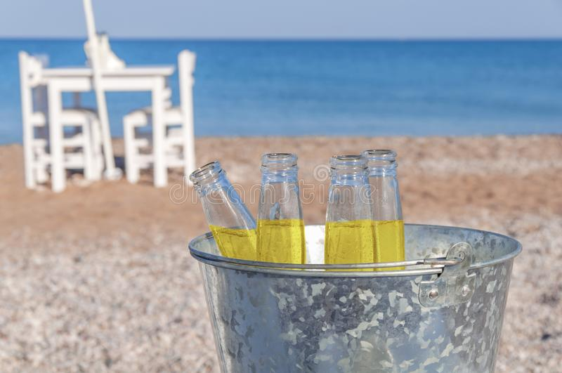 Bucket with four bottle of refreshment drink at sandy beach royalty free stock images