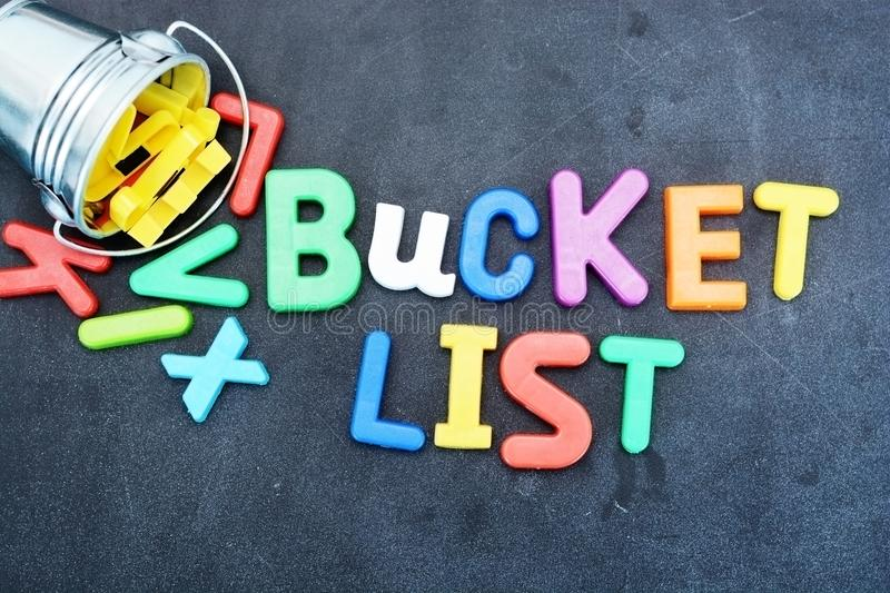 Bucket list concept, things to do in life with iron bucket and magnetic letters on chalkboard royalty free stock images