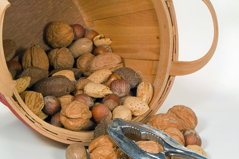 Bucket of Mixed Nuts. Spilled bucket of mixed nuts with nut cracker royalty free stock image