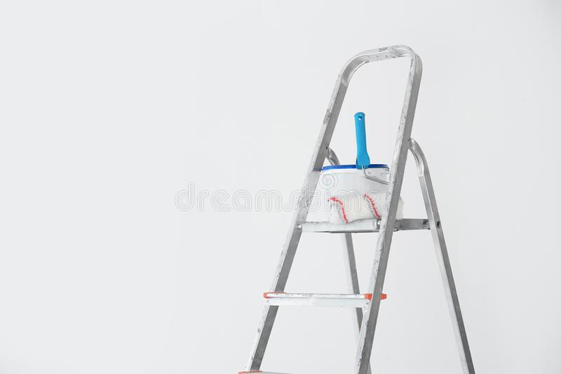 Bucket with paint and roller on step ladder royalty free stock photography