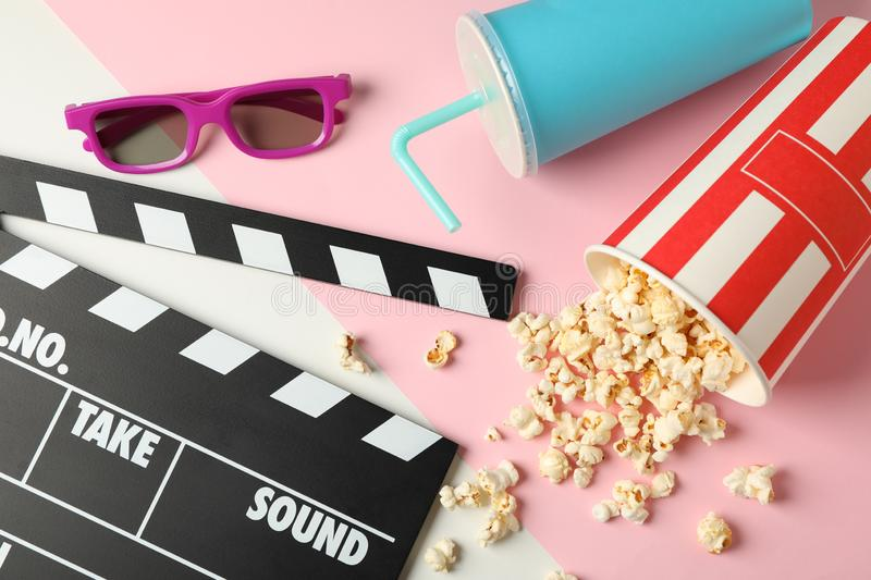 Bucket with popcorn, clapperboard, drink and 3d glasses on two tone. Background stock images
