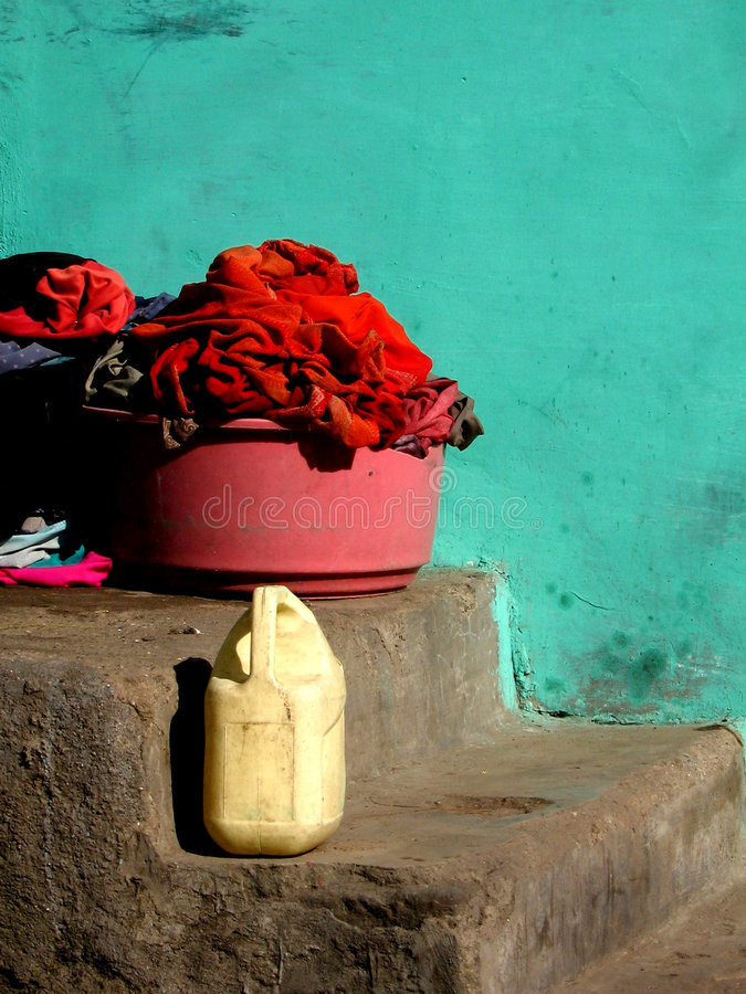 Bucket of Poverty. Bucketful of clothes in front of a bright colored wall in a traditional but poor Indian house stock photos