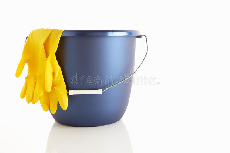 Bucket with rubber gloves royalty free stock photography