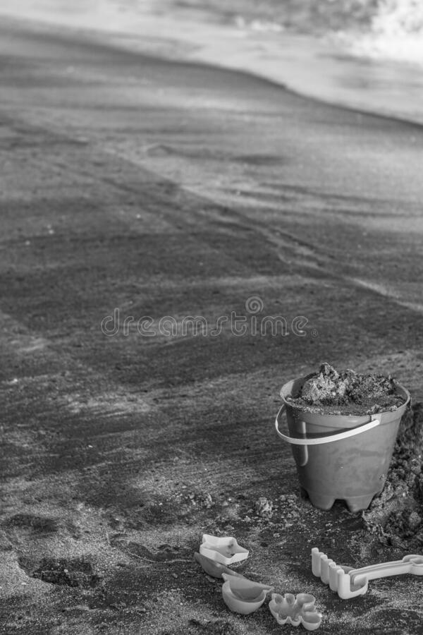 Bucket in the sand on a beach. Bucket in the sea sand black and white, at the corner of the image, toys for kinds build a castle in the beach closer to the sea stock photography