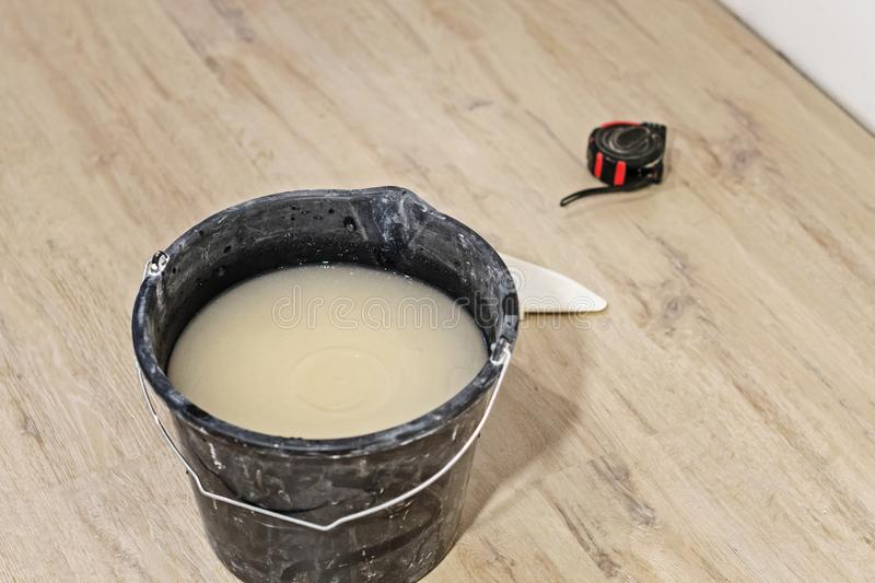 Bucket of Wallpaper glue on the floor. home repair. Bucket of Wallbucket of Wallpaper glue on the floor. home repairpaper glue on the floor. home repair royalty free stock images