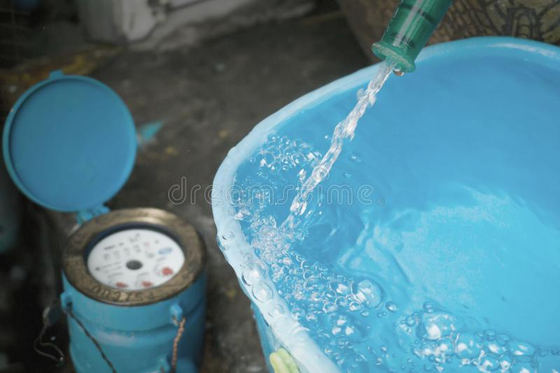 Bucket with water overflowing. And water meter behind scene. stock image