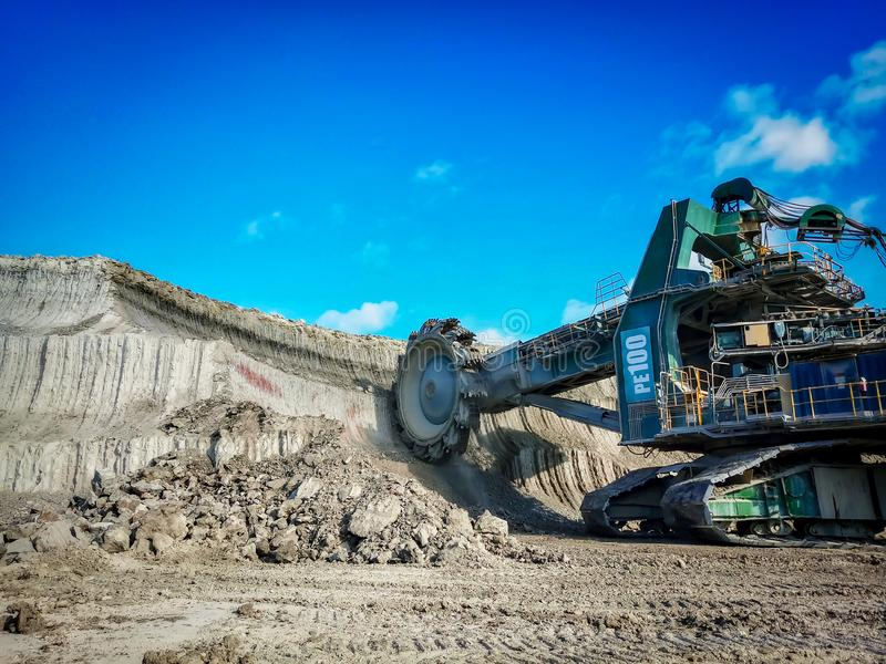 Bucket wheel excuvator is digging a soil in coal mine. royalty free stock photography