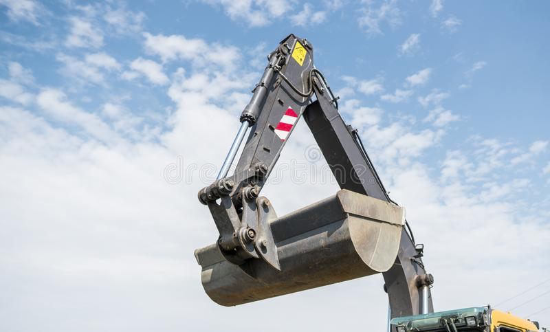 Bucket of yellow excavator loader standing against sunny cloudy sky during road construction and repairing asphalt royalty free stock photography