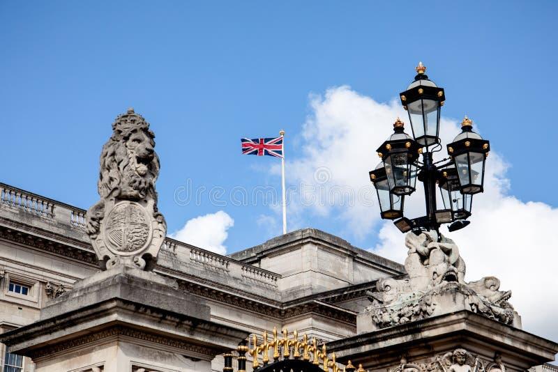 Buckingham Palace with british flag, lion with king crown, royal family. LONDON, UK - May 4, 2019. Buckingham Palace with british flag, lion with king crown stock photos