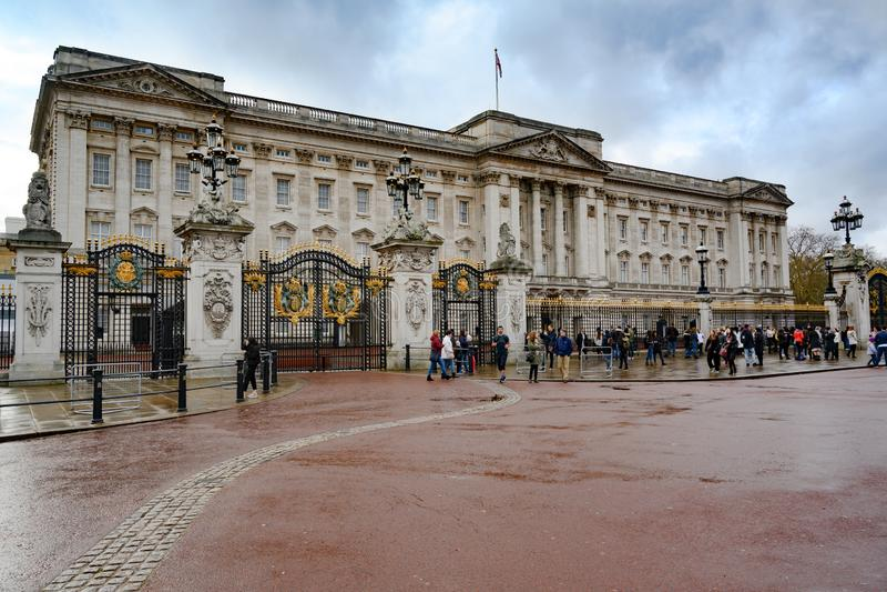 buckinghamengland london slott Folk som framme väntar av portar av Buckingham Palace royaltyfria foton