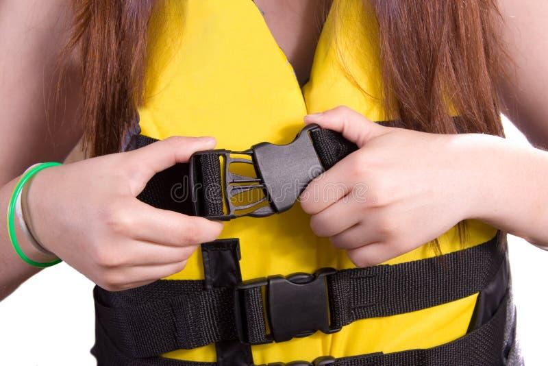 Buckle Up. Girl Fastening buckle on life jacket/ski vest stock image