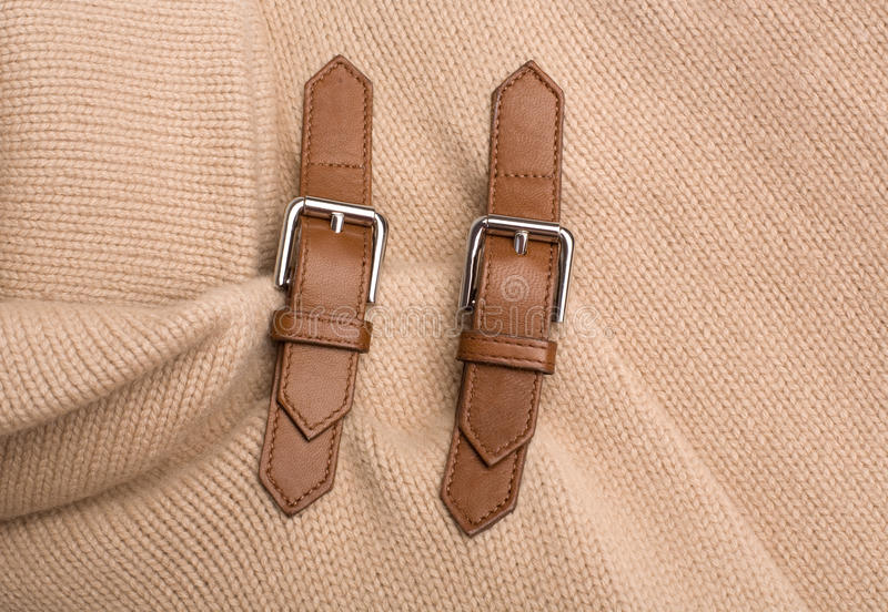 Buckles. Two buckles on beige knit sweater royalty free stock images