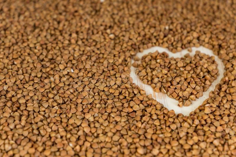 Buckwheat background with drawn heart. Gluten free and healthy diet. Shallow depth of field.  stock photography