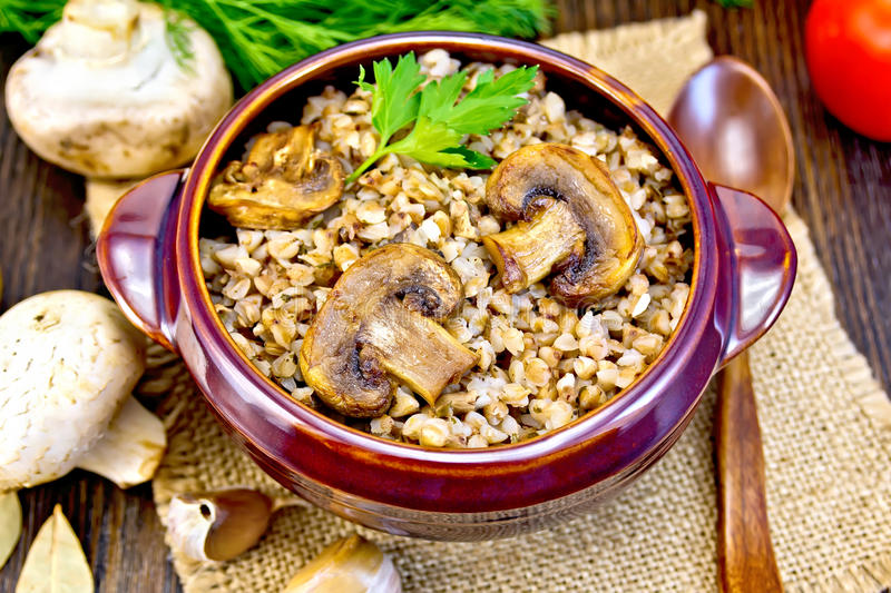 Buckwheat with champignons in clay bowl on table stock photo